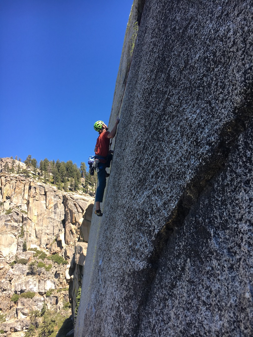 Hayden Miller face climbing on pitch three of A Bridge Too Far.
