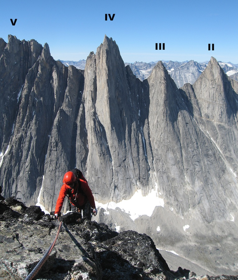 Dan McManus reaching the summit ridge of Hermelnbjerg's west summit after the first ascent of Ramblin' Man. Rising from the Hermelndal behind are the Tininnertuup peaks: V (1,706m), IV (1,725m), III (1,491m), and II (1,511m). The striking pillar on IV is taken by the 1,000m Norwegian-Swedish route, Qivitooq.