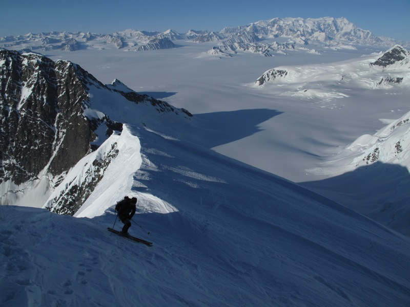 Tory Dugan departing the summit on the first ascent and ski descent of Peak 9,365', St. Elias Range, Alaska. Mt. Logan looms across the Columbus Glacier, 35 miles away.