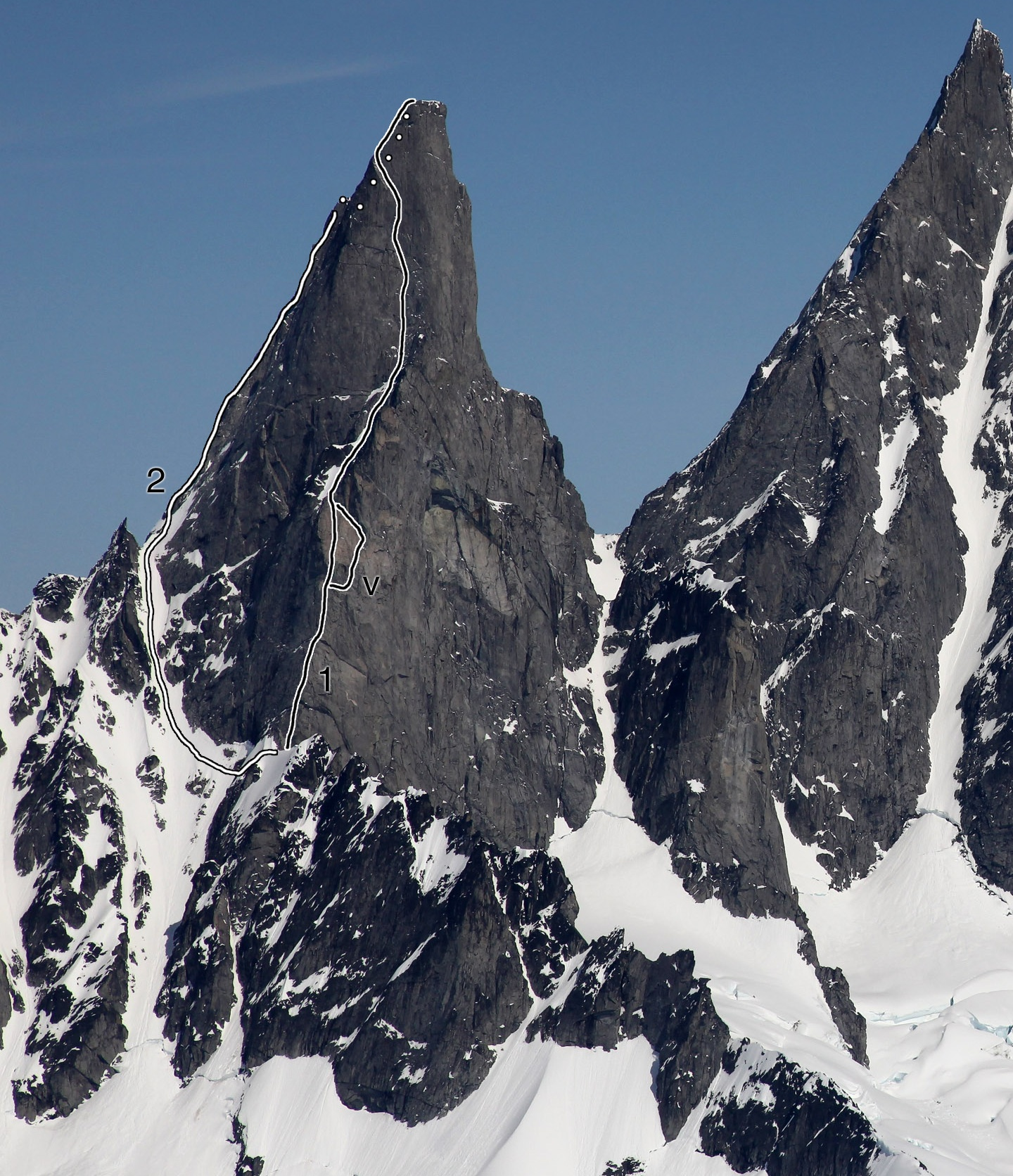 Burkett Needle: (1) South Pillar (Cauthorn-Collum-Foweraker, 1995), with (v) the 2009 Hasson-Holsten free variation. Not shown, on the steep face to the right, is the Heaton-Reichert 1995 attempt (see topo, AAJ 1996, p. 182) which ends high on what soon became the South Pillar; and Le Voyage des Clochards Celestes (Daudet-Foissac, 1999), which traverses into the face from the col on the right (the pillar rising east from the col is a sub-spire of Mt. Burkett). (2) Smash and Grab (Burdick- Frieh, 2009).