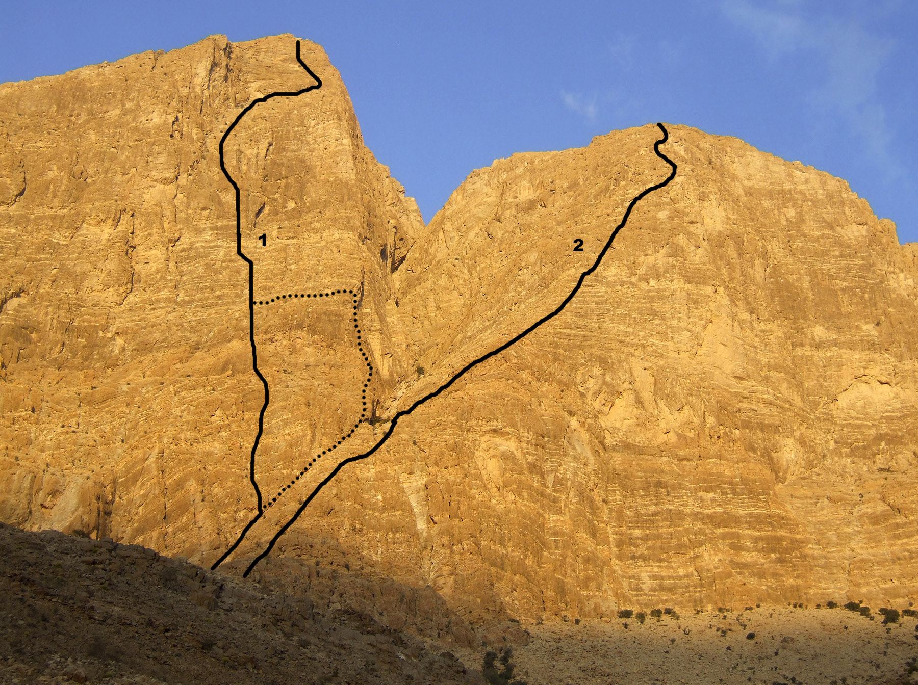 The southwest face of Jabal Kawr, showing (1) The Full Qaboos (Chaudry-Hornby, 1999, solid line; Eastwood-Ramsden, 1999, dotted line) on Kawr Pillar, and (2) Anhydrous Living on Mabos Pillar.
