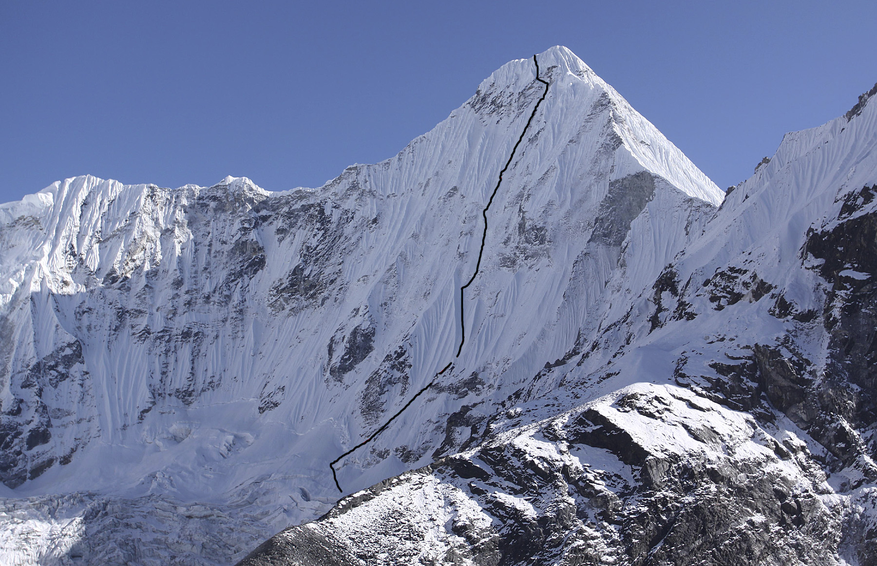 North face of Melanphulan with line of Polish ascent to northeast ridge, 100m from summit. The only previously recorded ascent of the peak, in 2000 by Supy Bullard and Peter Carse, climbed west face on right direct to summit.