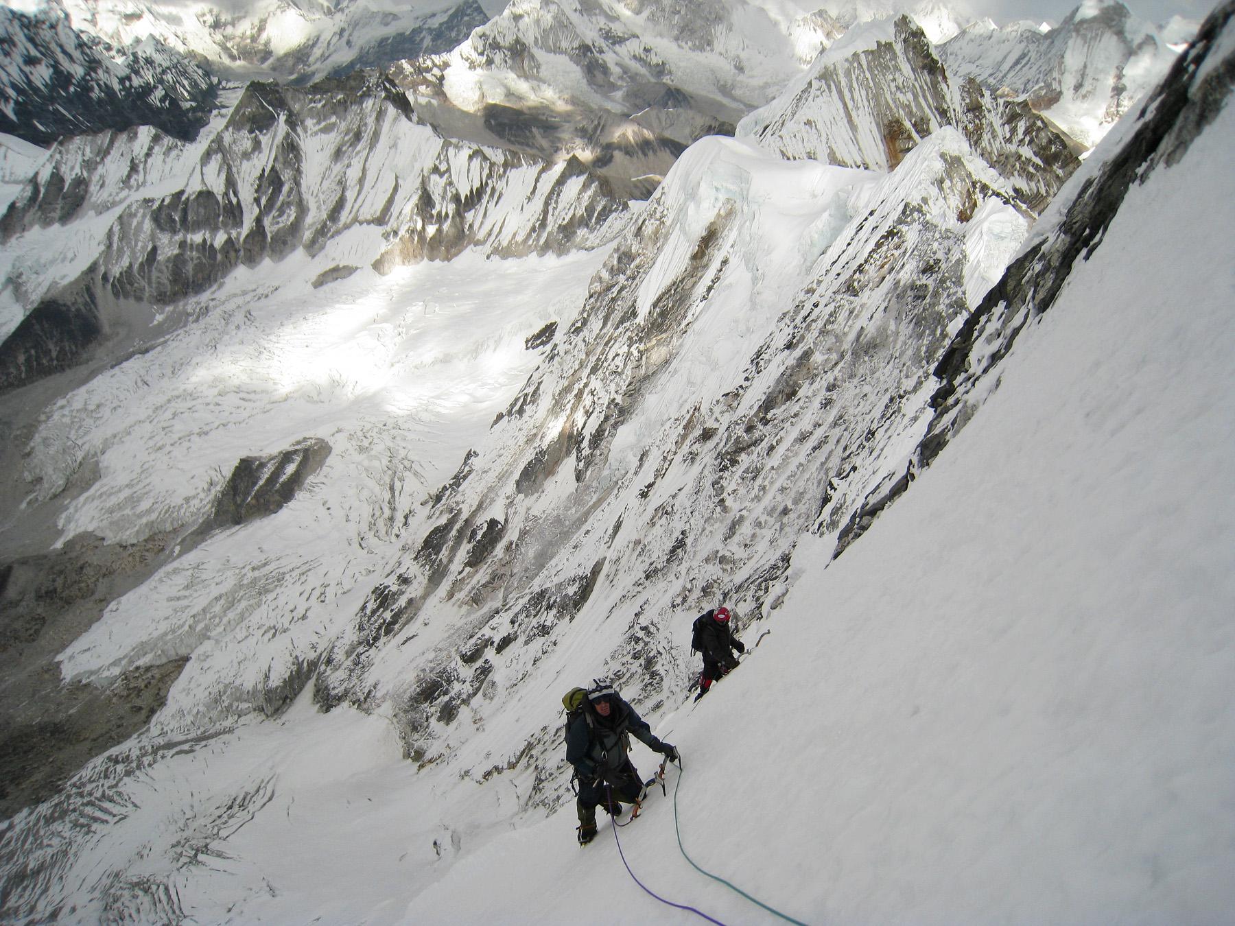 Marcin Michalek and Wojtek Kozub on upper part of north face of Melanphulan. Highest peak on continuation ridge behind is 6,473m; below is upper Nare Glacier.