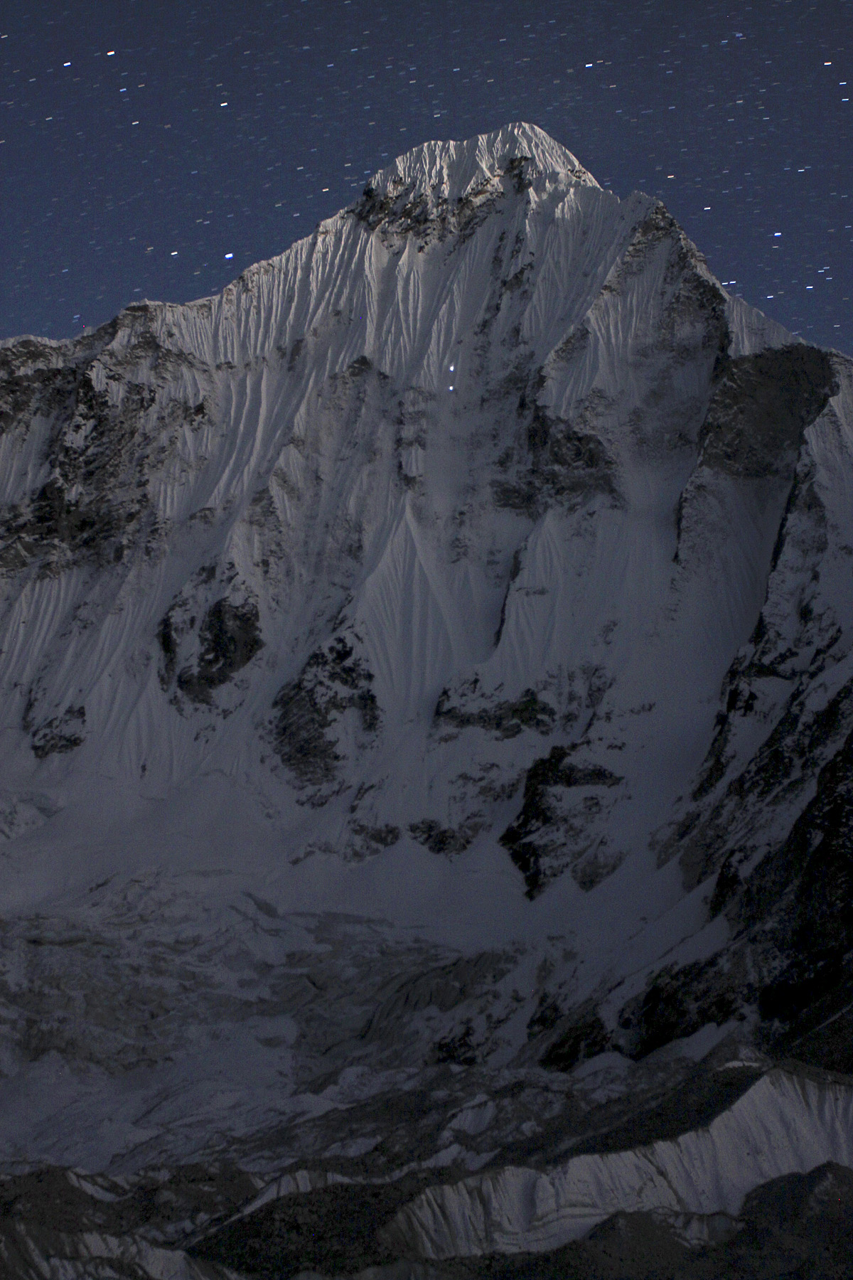 North face of Melanphulan seen at night from base camp. Lights from headtorches of two climbers are visible in upper third.