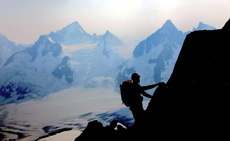 Nate Farr climbing the Dalestrom, with Mt. Endeavor prominent in the left-center skyline. The left skyline of Endeavor shows the upper one-third of Arête sans Chaussures