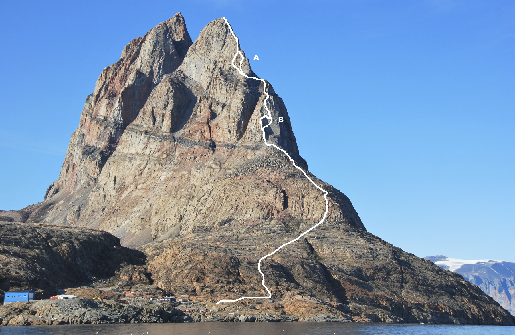 The south side of Ummannaq. The solid line shows the Chauché-Mackay Route, the dashed line, where it differs at points (A) and (B), the Doyle-Leinss Route. Both end on the south summit.