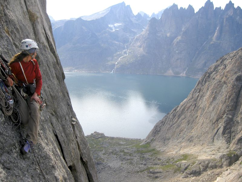 Danika Gilbert admires rock walls on the far side of the Torssukatak Fjord from a hanging stance on Blue Whale.