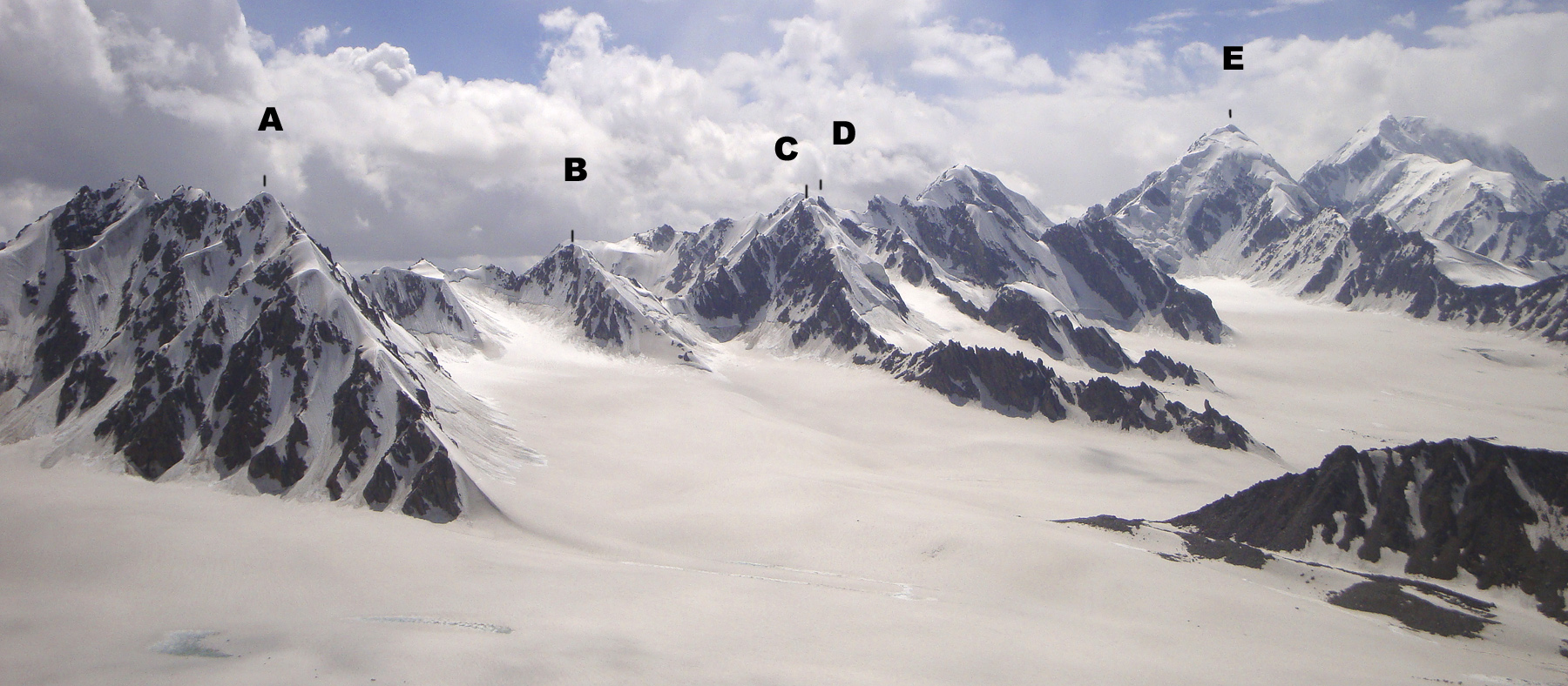 The expansive upper Qala-i-Hurst Glacier basin. (A) Koh-e-Beefy. (B) Koh-e-Baffa. (C) Koh-e-Forot Zorman. (D) top of unnamed peak attempted by Dutch. (E) Koh-e-Yakhi. Low rocky ridge in right foreground is southern end of Pt. 5,200m, climbed in 2008.