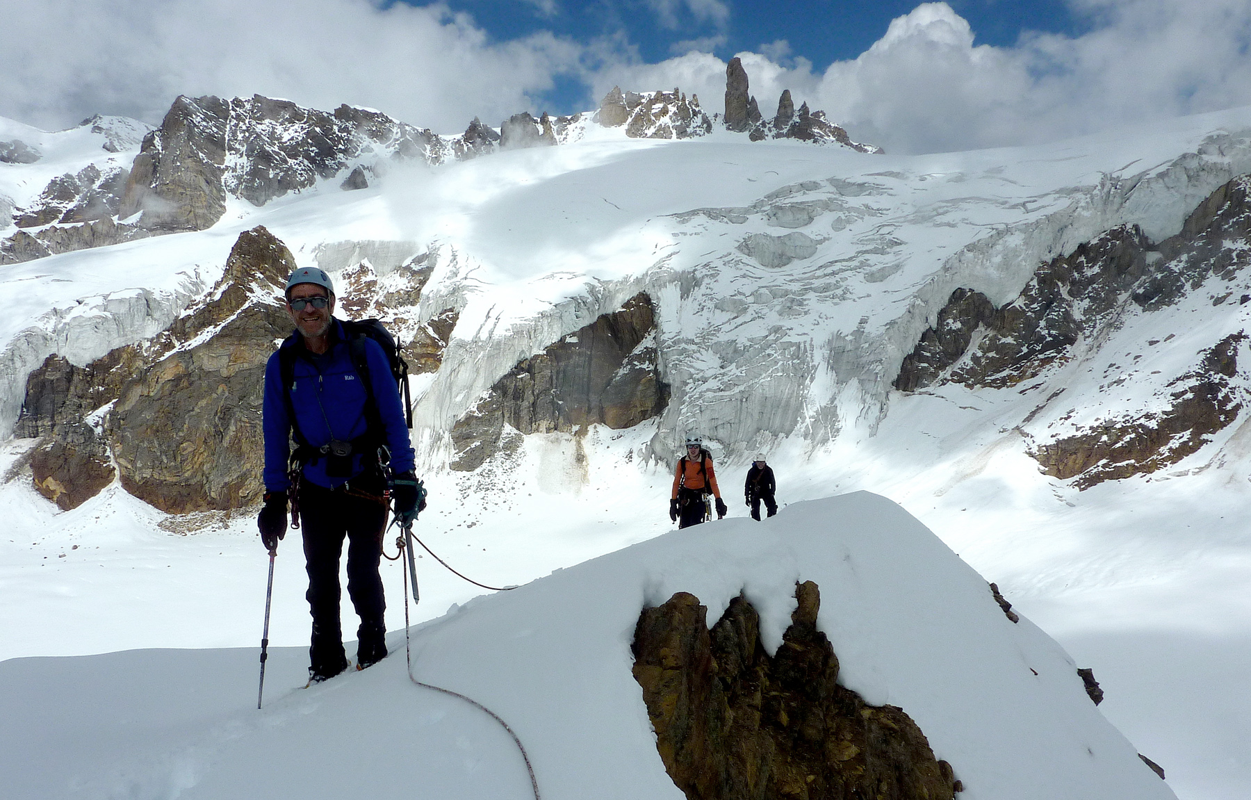 At the summit of Tribulation Point. Sentinel Peak is the rock summit immediately above the head of the foreground climber (Derek Buckle). Directly behind this is the broad-topped Snow Leopard Peak. The south wall, facing the camera, is split by an obvious broad couloir system. The route of ascent started right of this and slanted left up a ramp to its top. The rock on the splendid 'aiguille' looked superb, though it is a long approach for a short climb. Mike Cocker