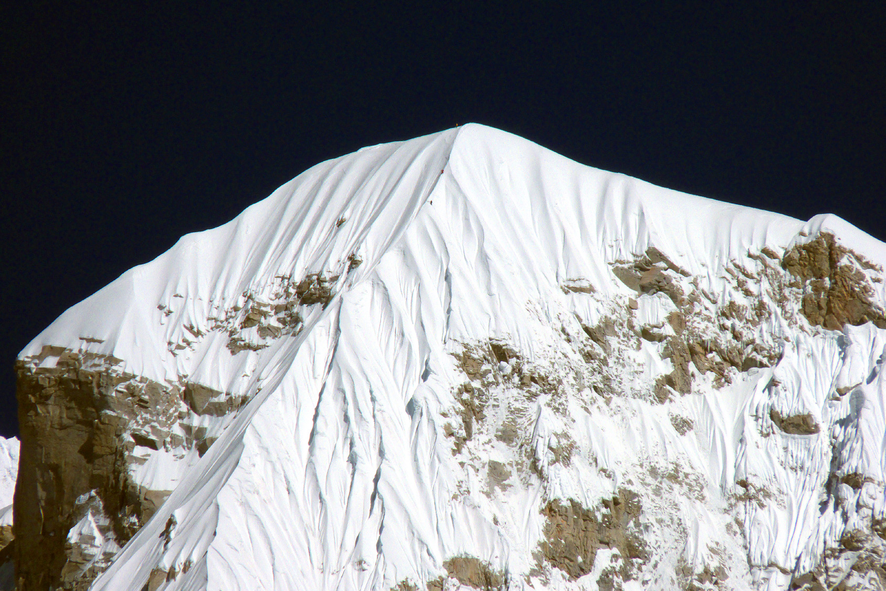 Summit of Lunag southeast. Two climbers can (just) be seen descending the final ridge. A third stands on the summit.