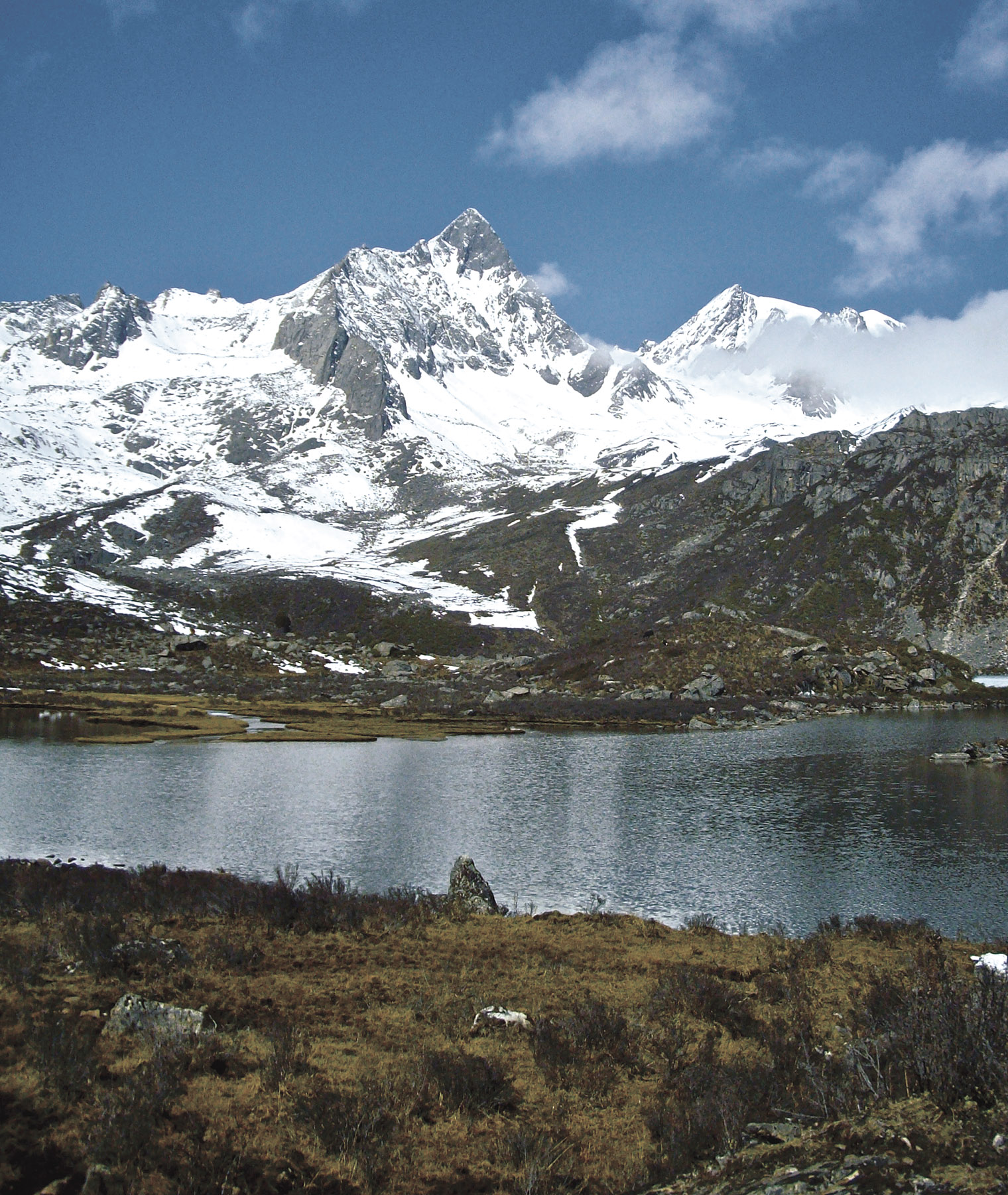 East face of Xiaqiangla and unnamed peak (right) seen from the shores of Da Haize. Route of first ascent of Xiaqiangla climbed hidden face behind steep right skyline ridge.
