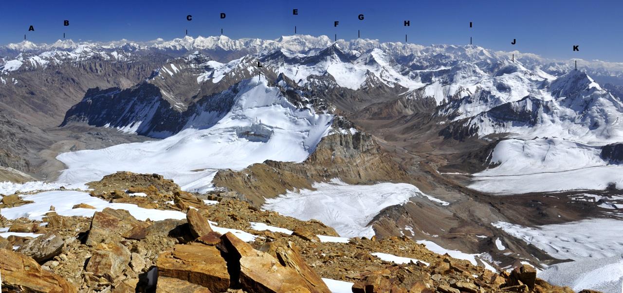 Panorama southeast from Pik Mayakovsky. High peaks in background form part of High Hindu Kush in Afghanistan's Wakhan Corridor. Near peaks form southern part of Ishkashim Range. (A) Koh-e-Hevad (6,849m). (B) Lhunko Massif (6,902m). (C) Akher Cioch (7,020m). (D) Koh-e-Urgunt (7,038m). (E) Saraghrar Massif (7,349m). (F) Pik Kharskhavol (Qullai Khirskhabol or Akademika Berge, 6,091m, first climbed in 1947). Snowy summit to its immediate right is Pik Imast (5,945m). (G) Koh-e-Shakhawr (7,116m). (H) Koh-e-Kishni Khan (6,755m). (I) Noshaq Massif (7,492m). (J) Pik Anbarku (5,838m). (K) Pik Kolbun (5,864m). In front of this peak and just off picture to right is Abkharv Pass. (L) Pik 5,702m.