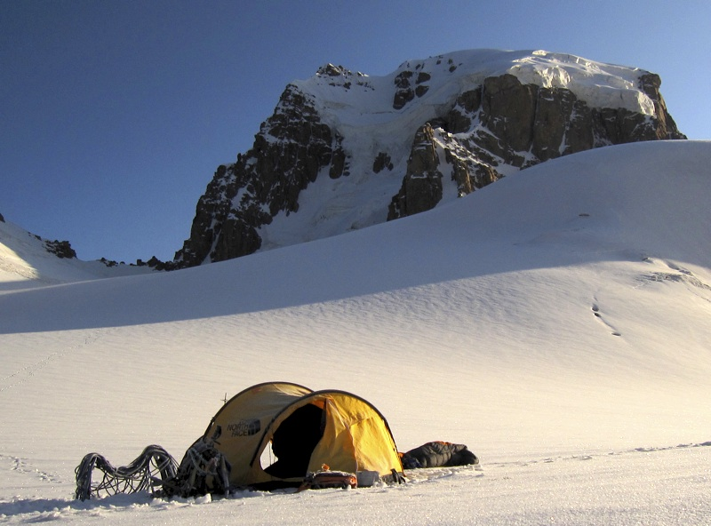 Morning sun strikes camp on 4,900m col south of Byeliy. Slovenian route follows snow and ice through buttress/ridge facing camera, over capping seracs, and left up easier snow slopes to summit. In 2000 Americans, approaching from China, attempted left ridge, completing rock section before thunderstorm forced them down from snow arête 200m below summit.