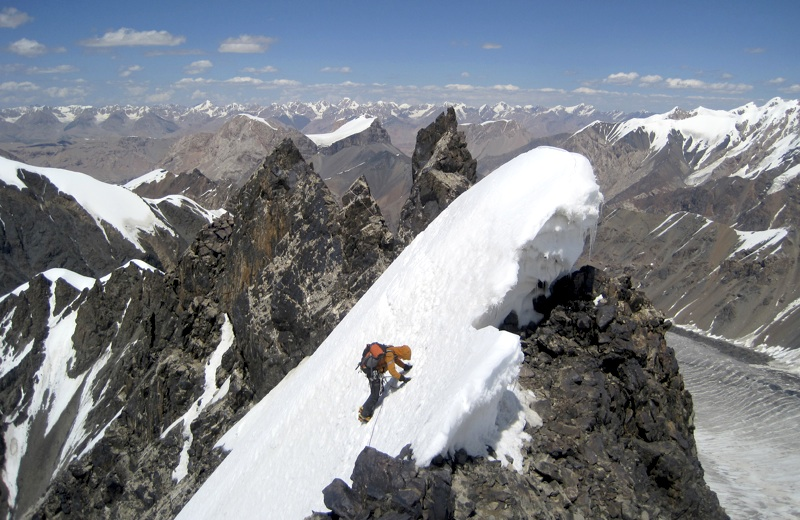 Charlie Evans traversing north ridge toward summit headwall. Sarychat Glacier down to right. Peaks of Borkoldoy Range in distance.