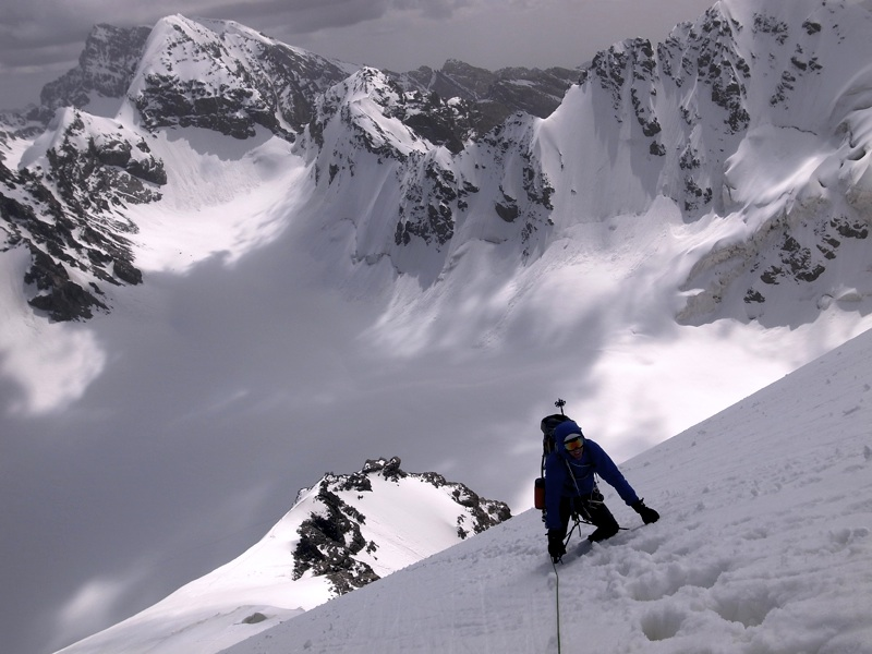 Jim Broomhead on middle section of Bivouac—French for Mistake, Pik Alexandra. Below is Chulaktor Glacier. Behind lie unclimbed peaks on frontier ridge: Pik 5,112m (far distance), Pik 5,025m, Pik 4,801m, and, on right, part of north face of Pik 4,881m.