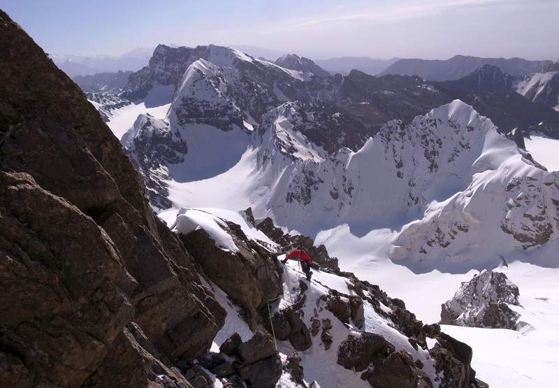 Jim Broomhead on upper ridge of Pik Alexandra. Behind is frontier ridge. In distance is broad-topped Pik 5,112m. Closer lie Pik 5,025m, Pik 4,801m and, nearest, snowy pyramid of Pik 4,881m.