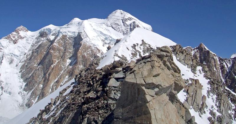 Climber stands on summit of Junai Kangri. Behind lies great south face of Mamostong Kangri. Jonas Cruces