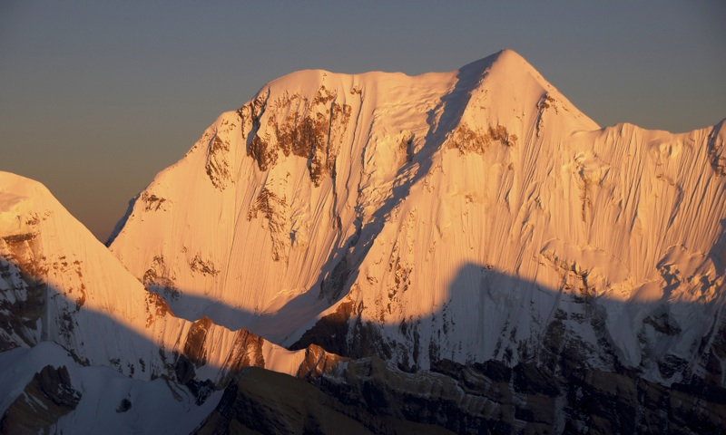 """Kanjiroba, with elegant northwest ridge falling from south summit (6,883m). Japanese climbed """"northwest ridge"""" of Kanjiroba in 1979, but their account states they made Camp 3 (6,580m) before Kanjiroba North (rounded shoulder at left end of north ridge, 6,858m, unclimbed) and traversed below it, implying that they followed left skyline ridge in image. Other four ascents of Kanjiroba South followed south face and southeast ridge, first climbed in 1970 by Japanese."""