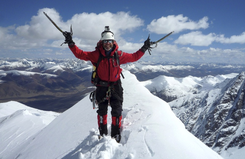Tim Church on summit of Nideng Gongga. Beyond him to northeast is Hati Group, while barren valley below leads off-photo left to Zhopu Pasture. Rock ribs bottom right fall from northeast ridge of Xiashe.