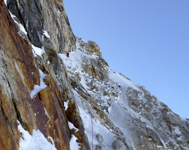 Zhou Peng on rightward traverse between two couloirs, Jiazi west face.