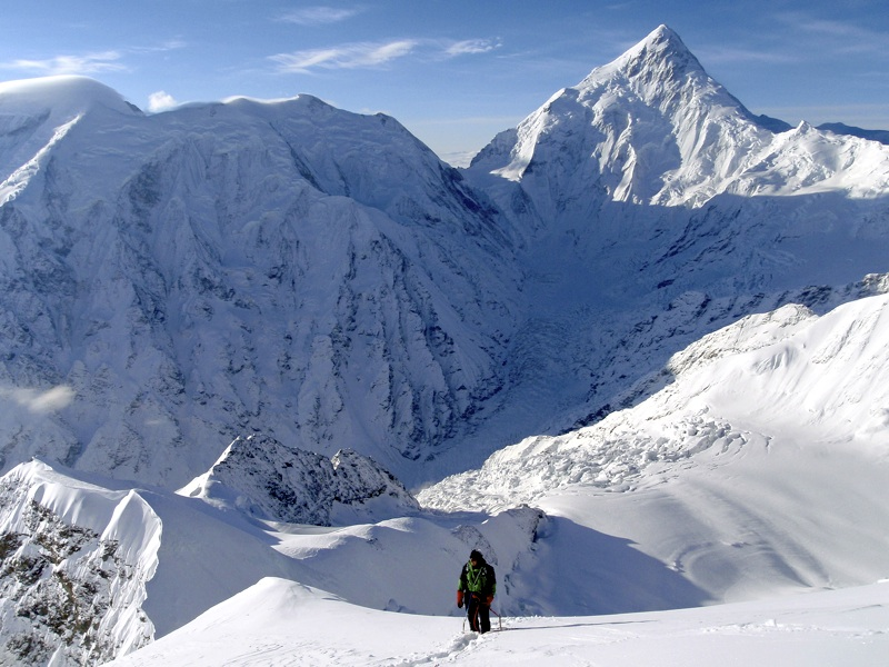 On summit ridge. Broad-topped peak to left is Zhong Shan (Sun-Yat-Sen, 6,886m, second highest peak in Minya Konka Range). Pyramid is 7,556m Minya Konka; first ascent, by Americans in 1932, followed northwest ridge (right skyline).