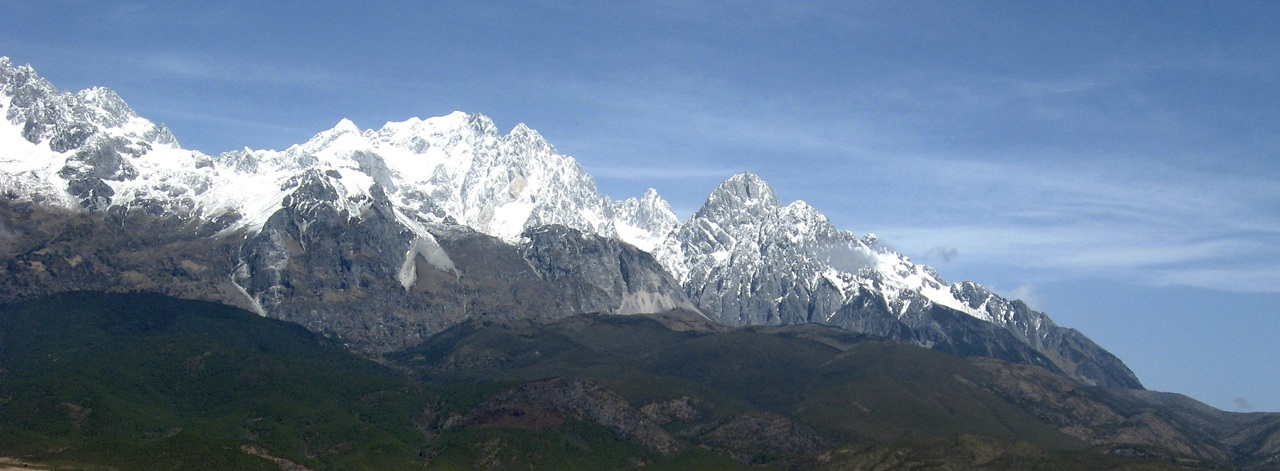 Yulong Xueshan from south-southeast. Smaug just visible in top left corner. Shanzidou is large mountain in middle. Predominantly rocky summits on right lie on east ridge of Shanzidou.