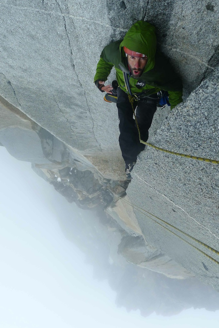 Pedro Angel Galan Diaz pauses on the 22nd pitch (6c) of the southeast pillar, as the rock fades into the fog below. The team experienced a multitude of bad weather, which nearly destroyed their portaledges.