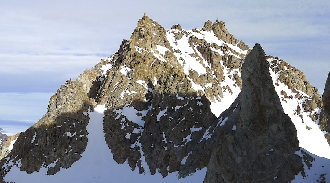 Blue Dragon's Thumb (the nearest of the two distant summits) seen from Made in Greenland. The climb started in the main snow couloir below and left of the summit, then from the top climbed hidden gullies and chimneys to the right. The highest point is hard to distinguish from this angle.