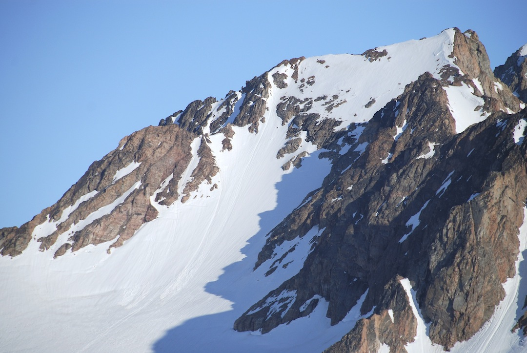 Snow Blade. The route of ascent climbed snow toward the left side of the face to reach the left skyline ridge, then up this to the north summit.