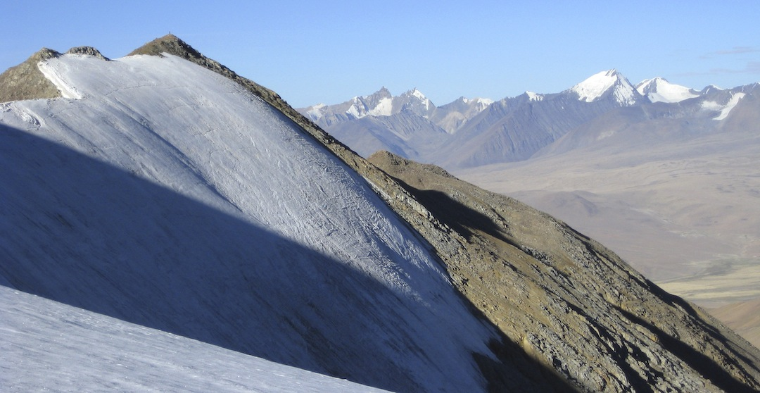 The rocky summit of Peak 6,087m (the small dot on top is Matt Dettinger) in the Linzhou Range, with part of the Loinbo Kangri Range behind.