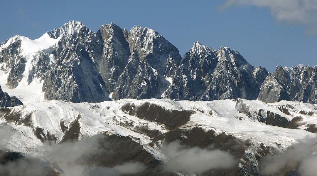 East side of the highest peaks of the Gangga, which lie in the northern part of the massif. The highest summit visible is Gangga I (5,688m). The two summits immediately right are Gangga Central (5,670m) and Gangga North (5,650m). Other summits are unnamed.