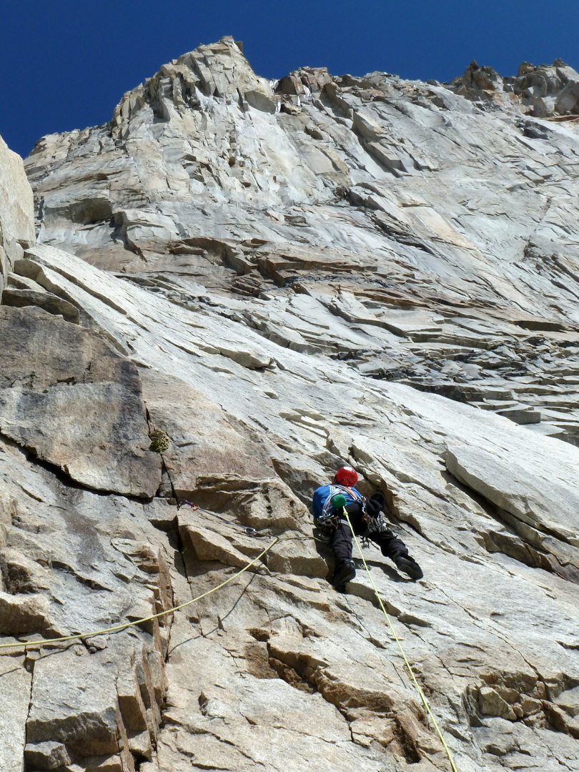 Myles Moser leading up featured granite below the steep upper headwall on Plate Tectonics, North Tower of Paine.