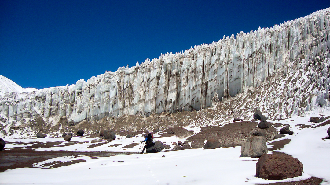 Resting below an ice wall on the Ojos Del Salado–Pissis traverse.