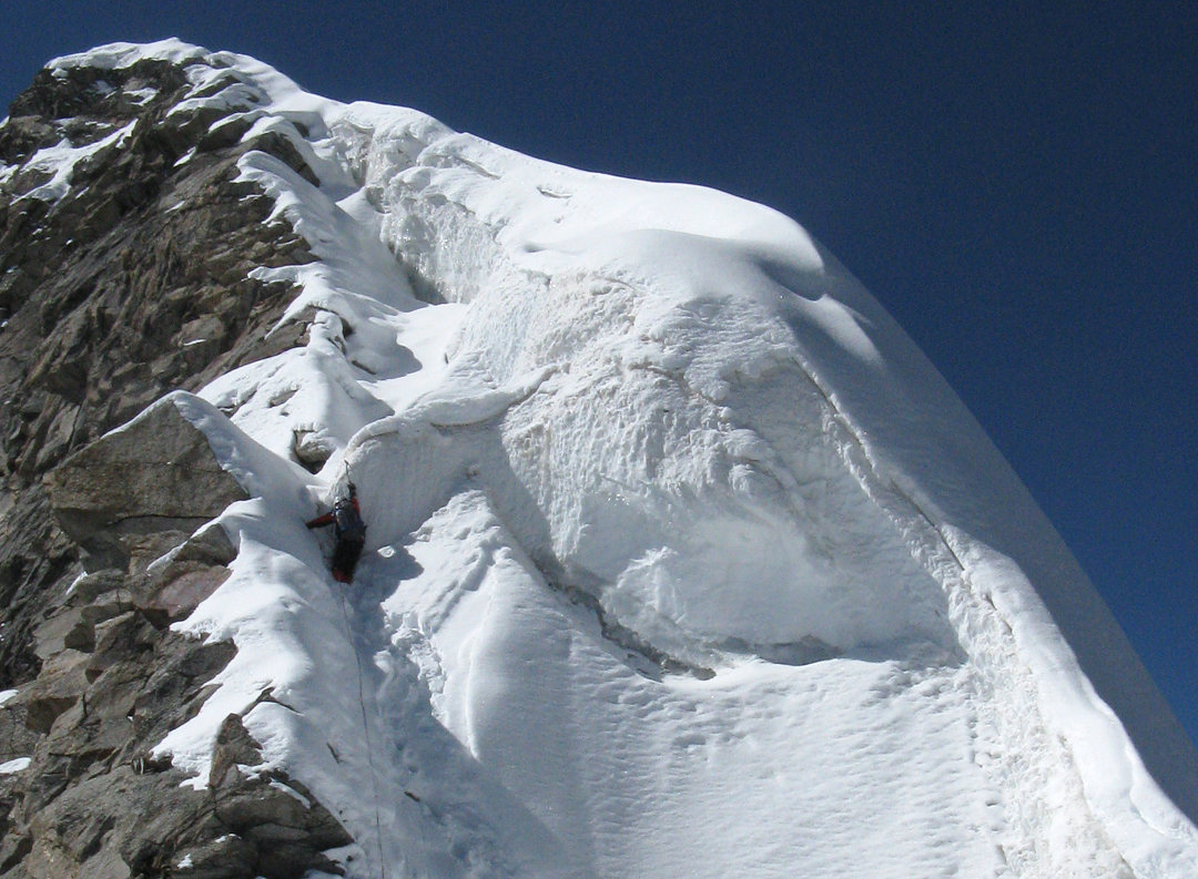 Steve Burns bypassing the steep snow step on the upper east ridge of Shakkar Peak.