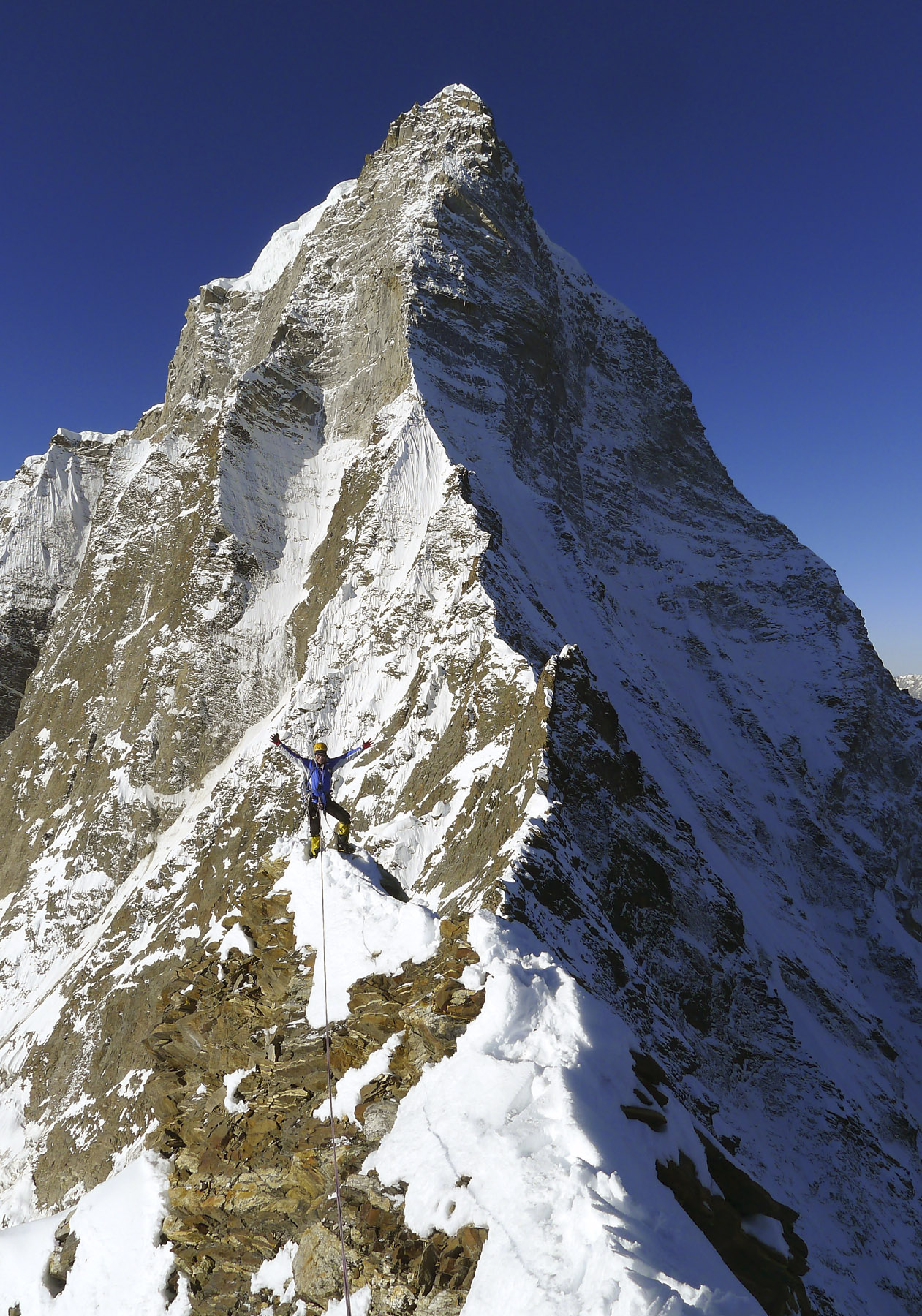 Mick Fowler on the summit of Point ca 5,500m, with the Prow of Shiva behind. Paul Ramsden