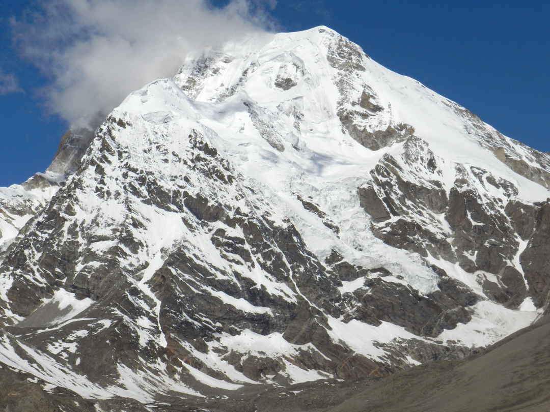 East face of Chomoyummo (Chomiomo, 6,829m) from the Plateau. Kellas made the first ascent in 1910 via easy snow slopes on the Tibetan flanks of the northeast ridge (close to, or behind the right skyline), a route repeated in 1945 by British, and again in 1986 by Indian military (Assam Rifles). While making an attempt on this route in 2005 several well-known Indian mountaineers, including the then vice-president of the Indian Mountaineering Foundation and two Everest summiteers, were avalanched and killed.