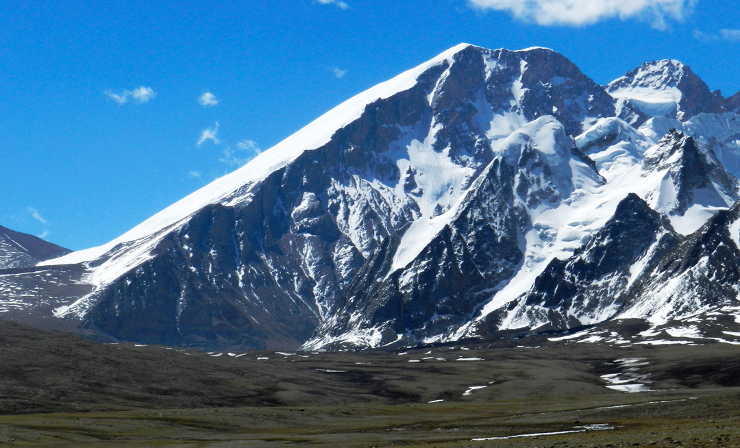 Pauhunri (7,125m) seen from Chholamo Lake (ca 5,000m) on the Plateau. When Dr Alexander Kellas made the first ascent in June 1910 via the obvious snowslopes (possibly behind the left skyline), Pauhunri was the highest mountain yet climbed, a record that would stand until the ascent of Jongsang in 1930. The summit to the right is 7,032m and unclimbed. Further south of this summit lie the high tops, 6,911m, 7,037m, 6,915m, and 6,730m, all unclimbed.  Harish KapadiaPauhunri (7,125m) seen from Chholamo Lake (ca 5,000m) on the Plateau. When Dr Alexander Kellas made the first ascent in June 1910 via the obvious snowslopes (possibly behind the left