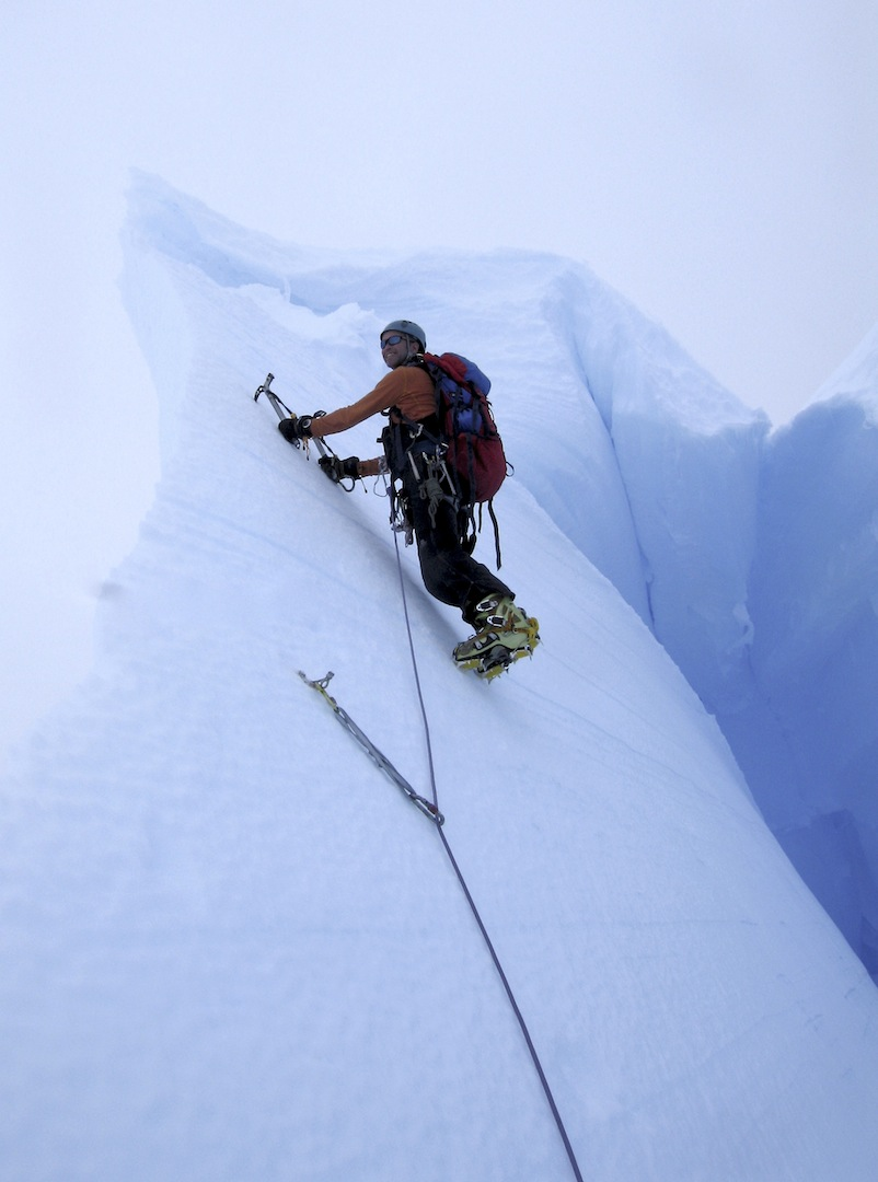Phil Wickens climbing through a large crevasse on the first ascent of Peak 1,333m.