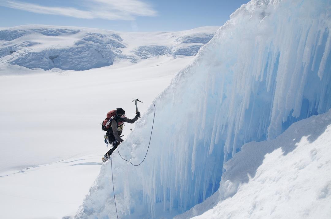 Hannah Baker climbs a steep ice arête just above the major crevasse on Peak 1,475m.