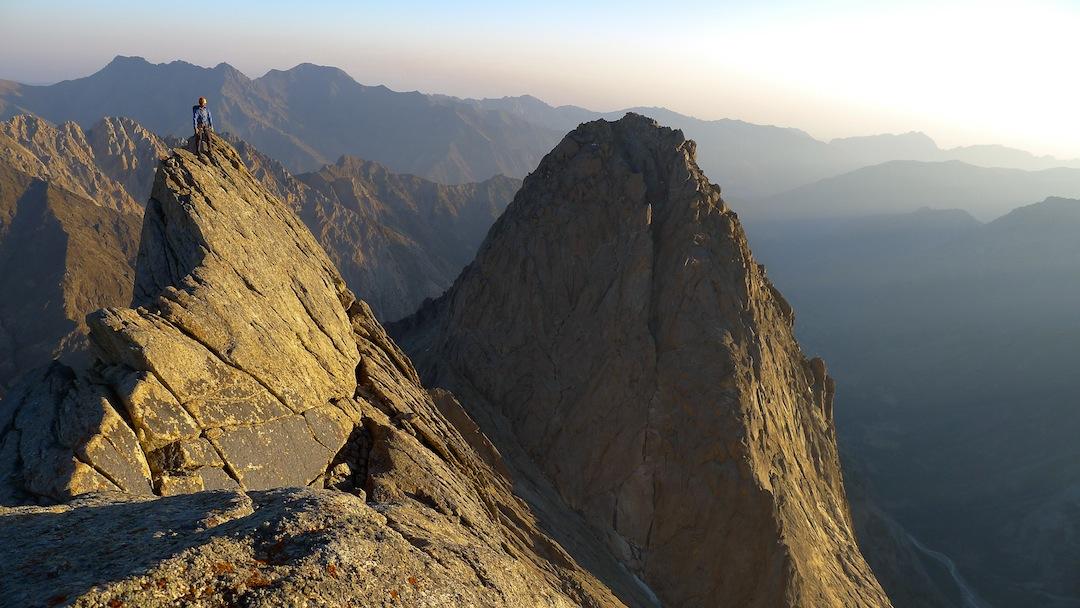 Josh Finkelstein on the beautiful ridge between Peak 1,000 Years of Christianity and Kotina (background).