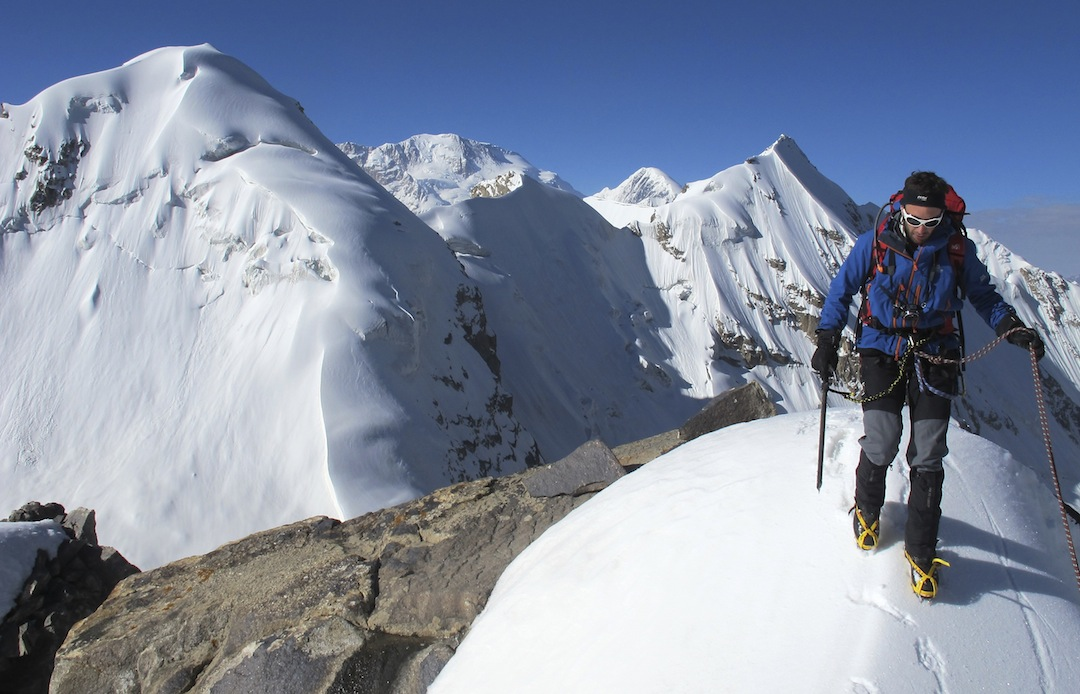 Arnaud Pasquer on the summit of White Pyramid. In the distance, to the southwest, is the broad north face of the Noshaq massif (7,492m). To its right the flat-topped dome-like peak is Gumbaz-e-Safad (6,800m).  Unknown peaks of the northern Mandaras Valley in the foreground.