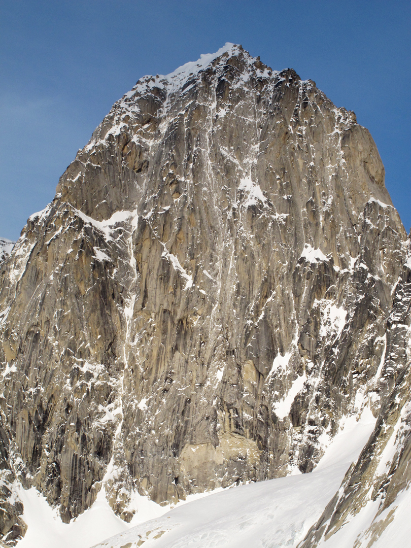The 3,400-foot west face of unclimbed Pyramid Peak. The author made two attempts on the obvious ice line but was stopped by overhanging snow mushrooms. A massive WI6 pillar hangs 2,000 feet up the route.