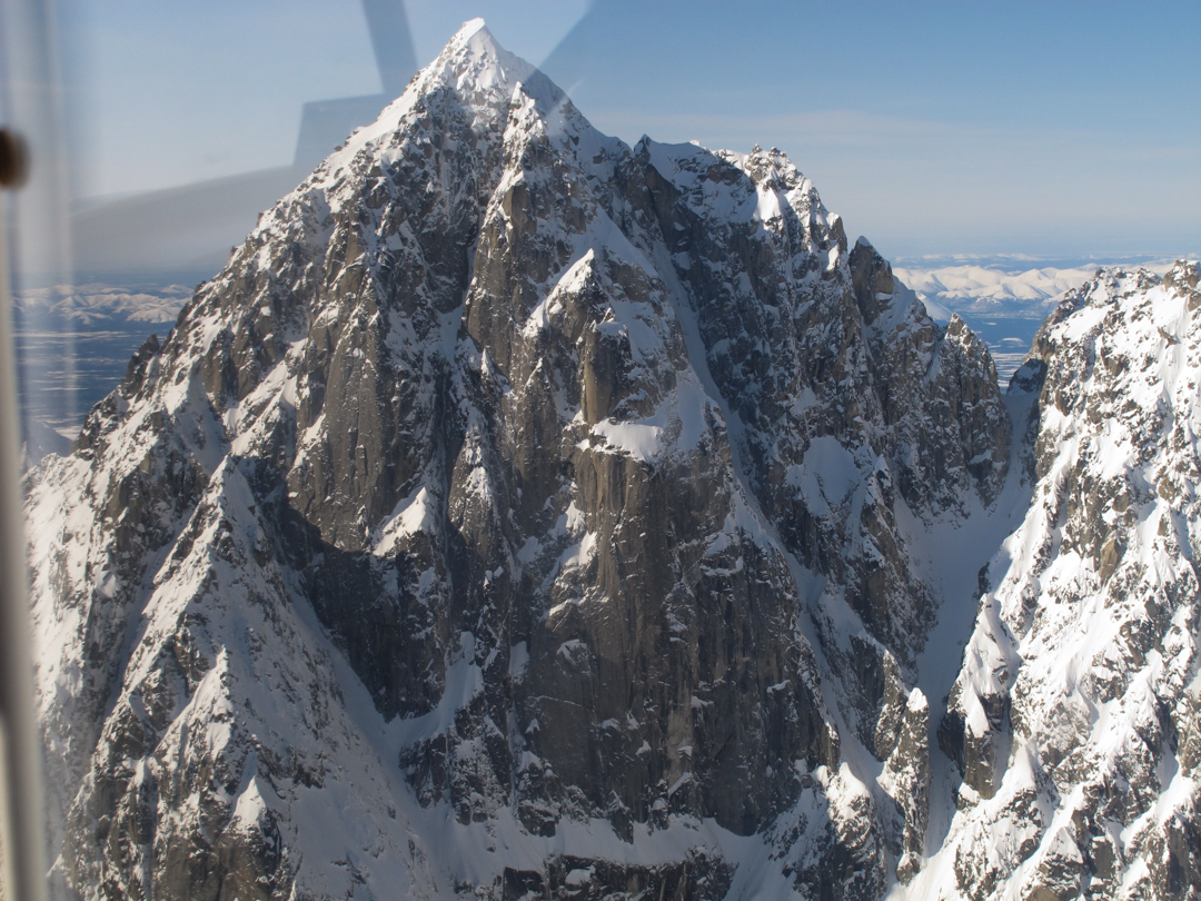 The 3,400-foot east face of Golgotha. Clint Helander and Ben Trocki attempted the direct route up an ice couloir splitting the face in 2012, but were driven off by spindrift. Instead, they completed the first ascent of the 8,940-foot peak via the ice ramp to the southeast face on the left.