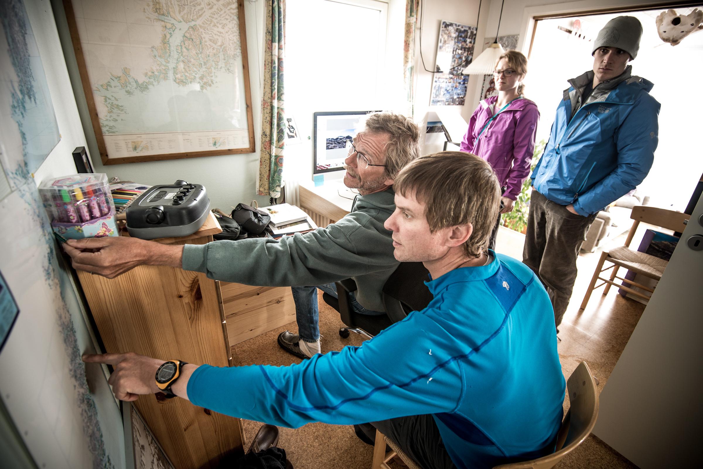 Libecki and team study maps at Hans Christian Florian Sorensen's home in Tasiilaq.
