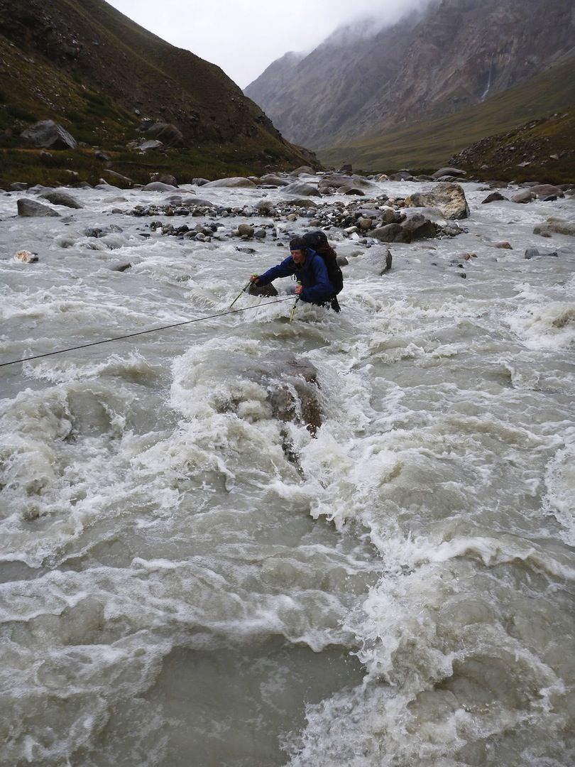 Harry Bloxham struggles to cross the fast-flowing Djangart River on his way back to base camp.