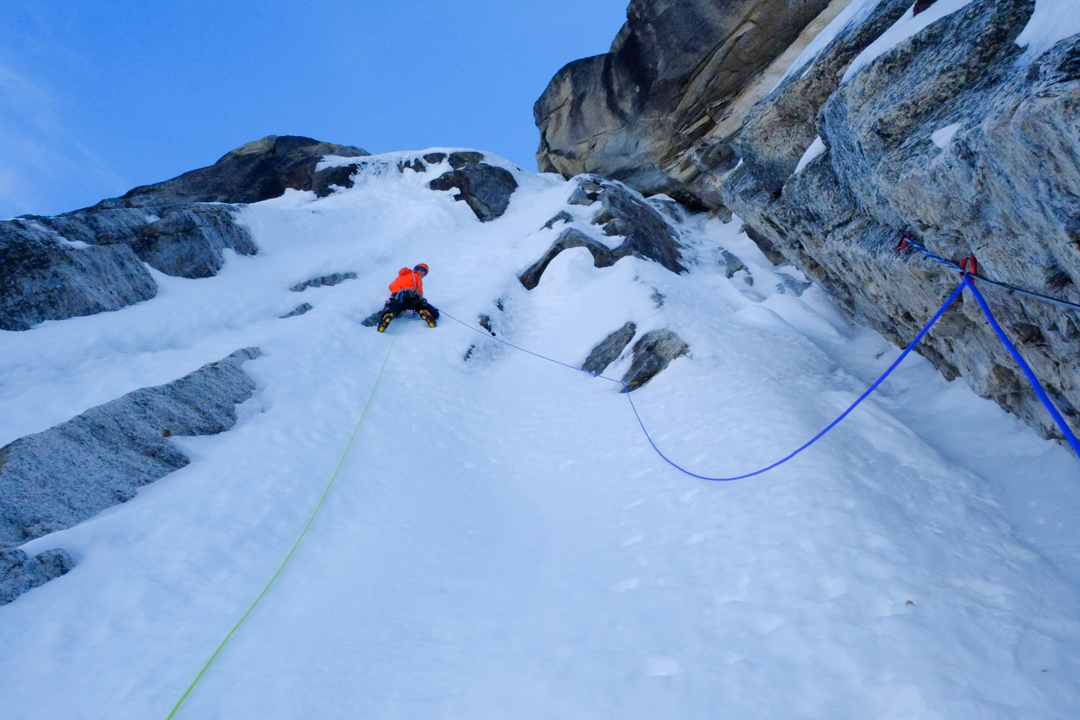 Jerome Sullivan climbing up the first of many steep pitches of unconsolidated snow on the Odyssey (1,100m, 6b A1 M7 90°).