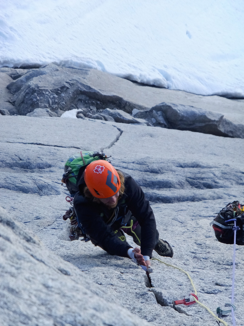 Max Fisher following a steep thin-hands crack on the third pitch of an attempt on Kooshdakhaa Spire's granite wall.