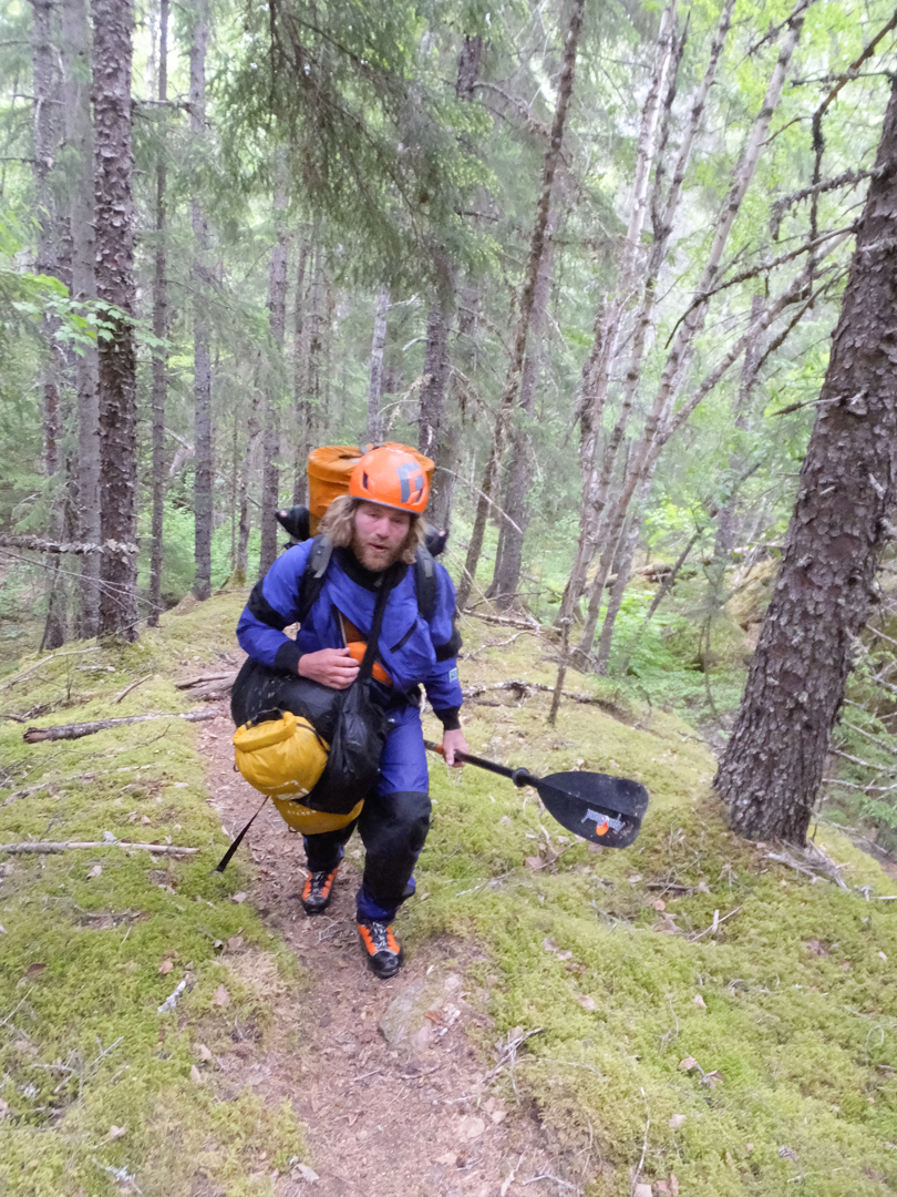 Max Fisher portaging on a frightening game trail in the lower Chilkat River Valley.