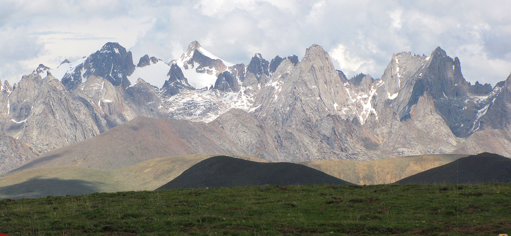 Nyainbo Yuze massif from the 4,398m Ronggeshan Pass to the northwest. The main summit is the snowiest pyramid left of center. Nyainbo Yuze II is the large black rock peak to its left.