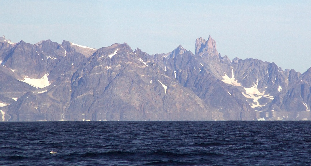 Kirken seen from the sea. The Austrian-Swiss pair climbed the right-hand and highest of the two prominent summits by the slanting face seen in profile to the left.